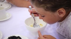 Beautiful girl in white eats corn flakes with milk in cafe Stock Footage