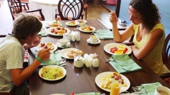 Serving table with lot of food and eating people mother and son Stock Footage