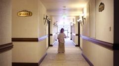 Pretty girl in ethnic dress runs in hallway of hotel Stock Footage