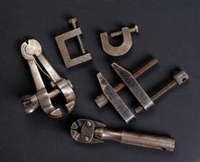Old metalwork screw clamps against a dark background - stock photo