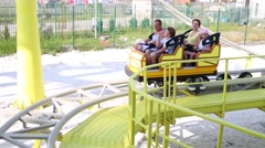 Family of four ride on attraction Roller coaster at sunny day Stock Footage