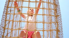 Girl inside cable cell in playground at sunny day, bottom view Stock Footage