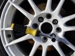 Cross wrench at installation of white custom car wheel - stock photo