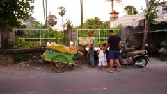 Street food vendor roasting sweet corn for two little girls Stock Footage