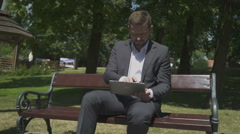 Businessman takes panoramic photo by tablet, sitting on wooden bench in park. Stock Footage