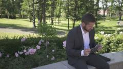 Businessman sits on wall in park and starts browsing tablet. Stock Footage