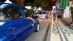 Blue taxi drive along busy and lively Balinese street at night, glide outside Stock Footage