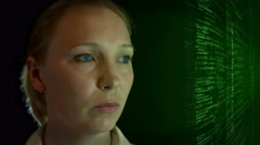 Female observer studying green lit code off to the side 4K - stock footage