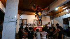 Ogoh-ogoh statue indoor preparation, children hold support pad Stock Footage