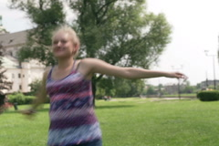 Happy girl twiddle in the park and smiling to the camera Stock Footage