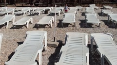 Toddler walks alone between empty sun beds Stock Footage
