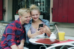 Couple sitting in the cafe and looking together on cellphone - stock footage