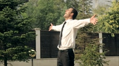 Happy Businessman in the Sunny Rain Takes Off His Tie Financial Freedom Concept - stock footage