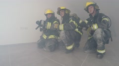 Firefighters get ready to apply water on fire in burning apartment Stock Footage