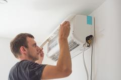 Master installing air conditioner . Industrial photo Stock Photos