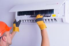 Placing back clean filter into air conditioner Stock Photos