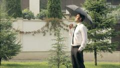 Businessman With Umbrella is Smiling in the Summer Rain Success Concept Stock Footage
