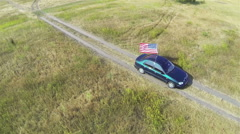 Car with  flag of  USA goes on a dirt road. Aerial  shot top view, scene four Stock Footage
