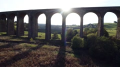 Low angle aerial shot of silhoutetted viaduct Stock Footage