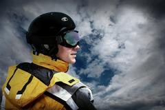 Stock Photo of Portrait of man wearing a helmet and glasses on the background of sky with cl
