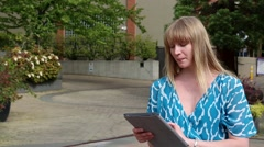 Young female using tablet computer outdoor, summer Stock Footage