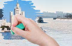 Hand deletes frozen Moskva river by rubber eraser Stock Photos