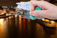 Hand deletes night scenery of Paris city by eraser Stock Photos