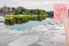 Hand deletes ice floe in winter river by cloth Stock Photos