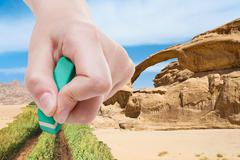 Stock Photo of hand deletes sand in desert by rubber eraser