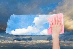 Hand deletes dark cloudscape by pink cloth Stock Photos