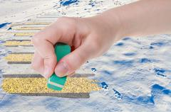 Hand deletes natural snow field by rubber eraser Stock Photos