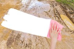 Hand deletes dirty country road by pink rag Stock Photos