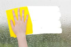 Hand deletes raindrops on glass by yellow rag Stock Photos