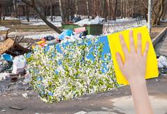 Hand deletes urban trash by yellow cloth Stock Photos