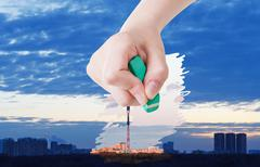 Hand deletes sunrise over city by rubber eraser Stock Photos