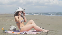 Attractive young woman suntanning on seaside beach. Stormy sea, windy weather - stock footage