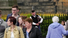 Scottish man playing the bagpipes in Edinburgh Scotland Stock Footage