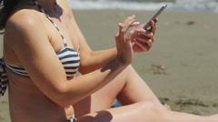 Young woman in bikini making selfie on smartphone, sharing photo on sandy beach Stock Footage
