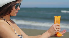 Young female applying sunscreen cream on shoulders, suntanning on beach at sea Stock Footage