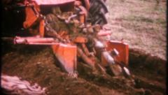 2383 - digging trench with farm equipment - vintage film home movie Stock Footage