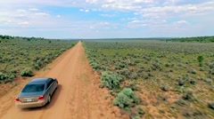 Car driving on a dirt road through iconic, dry Arizona landscape Stock Footage