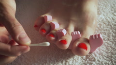 Closeup woman painting nails of her feet, applying red toenails. 4K Stock Footage