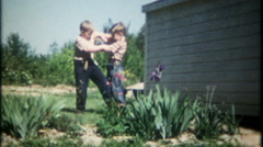 2390 - boys leg wrestle in the backyard at home - vintage film home movie - stock footage