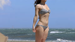 Young woman in swimwear standing on beach in stormy cold weather, sea waves Stock Footage