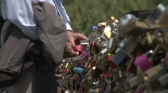 Hand Secures Lock on Love Locks Bridge - stock footage