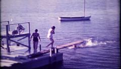 2400 - ladies use the diving board at the lake lodge - vintage film home movie - stock footage