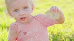 Cute blonde toddler outside in the sun with a cracker Stock Footage