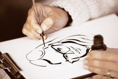 Female's hands drawing a caricature with black ink Stock Photos