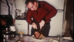 2397 - man cuts a large piece of meat on kitchen table - vintage film home movie - stock footage