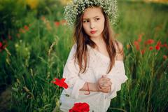 beautiful little girl posing in a skirt   wreath of poppies - stock photo